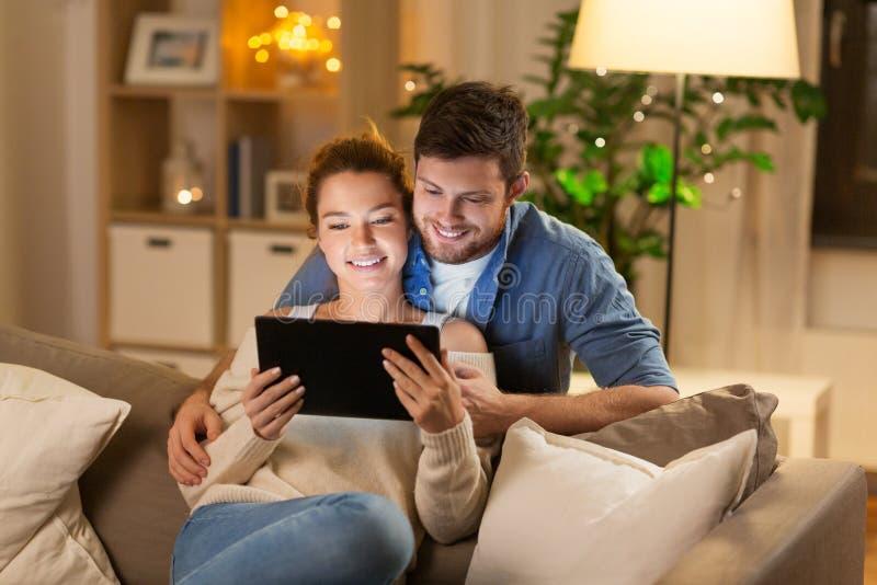 Gelukkig paar die tabletpc thuis in avond met behulp van stock fotografie