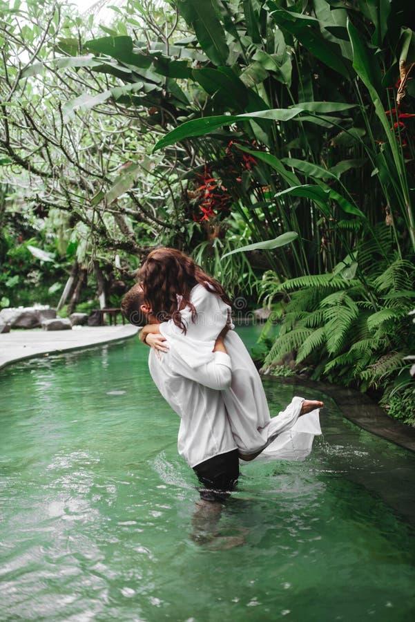 Gelukkig paar die terwijl het ontspannen in openluchtkuuroord zwembad kussen royalty-vrije stock afbeelding