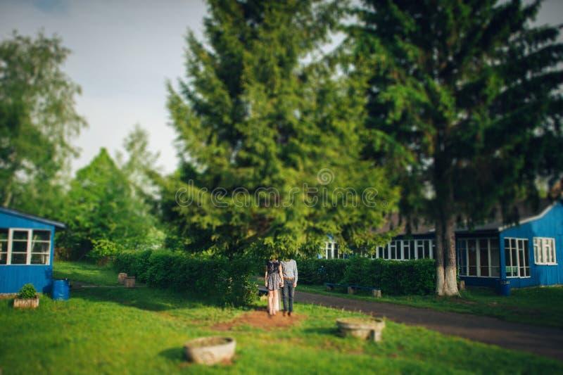 Gelukkig paar die in tuin voor blauw huis koesteren stock foto