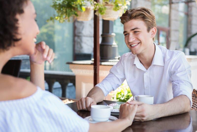 Gelukkig paar die tussen verschillende rassen bij de zomerterras flirten royalty-vrije stock foto