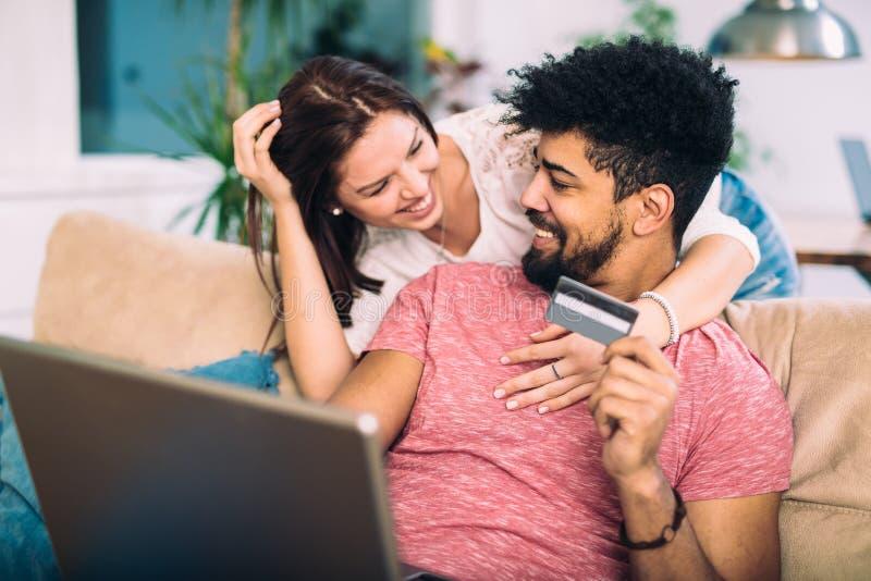 Gelukkig paar die tussen verschillende rassen online thuis winkelen royalty-vrije stock foto's