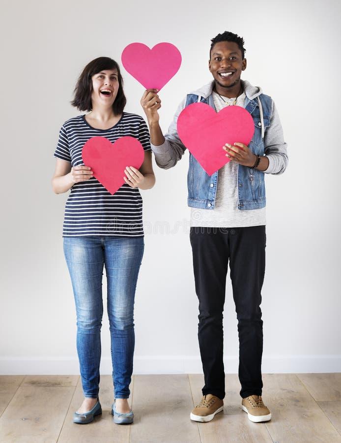 Gelukkig paar die tussen verschillende rassen rood hartenliefde en verhoudingsconcept houden royalty-vrije stock afbeeldingen