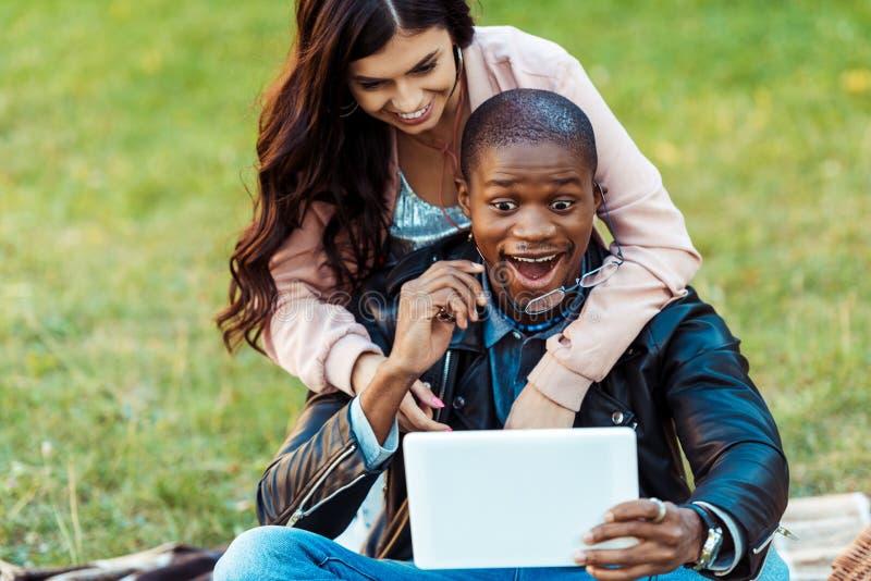 gelukkig paar die tussen verschillende rassen selfie met tablet bij nemen stock foto's