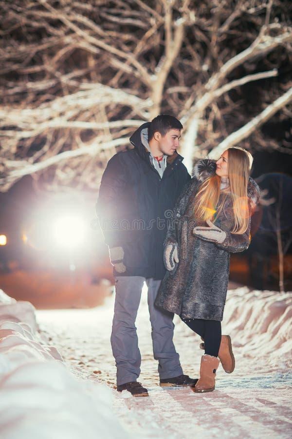 Gelukkig paar die van elkaar in nachtpark gefiltreerde foto houden met flitsgloed stock foto
