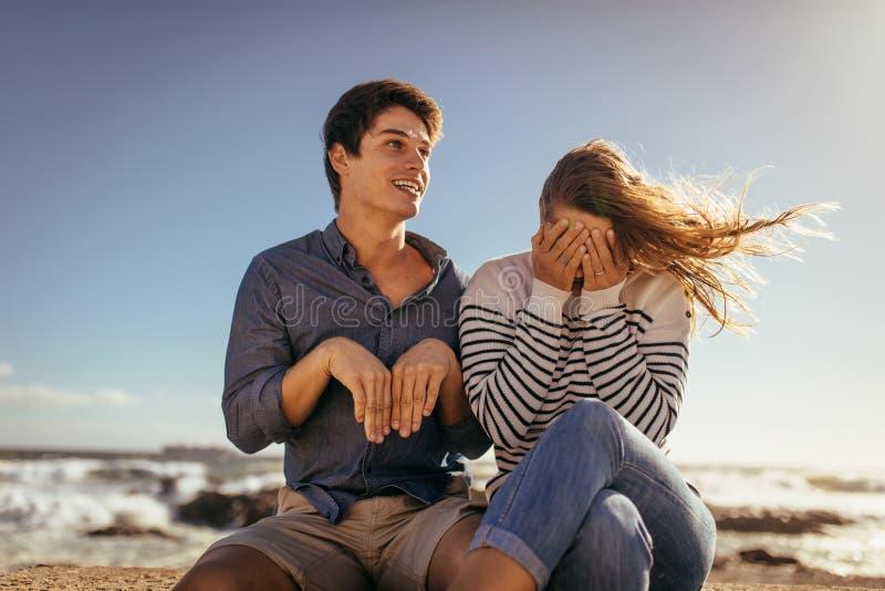 Gelukkig paar die van vrije tijd genieten en pretzitting op een overzees hebben wa royalty-vrije stock fotografie