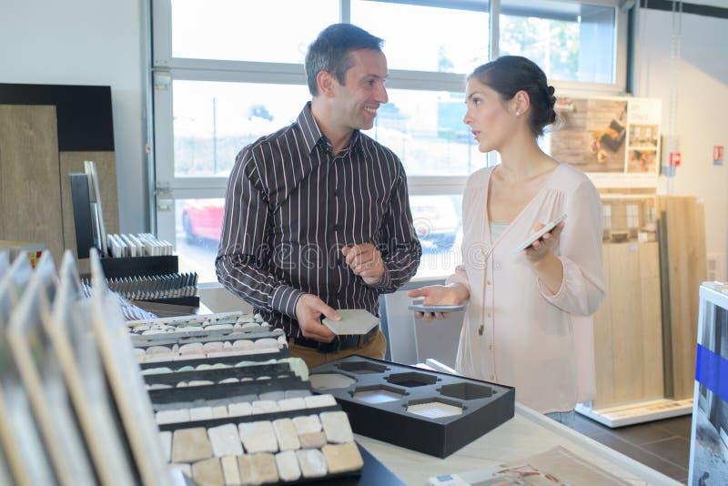 Gelukkig paar die voor het kopen van behang kiezen die ontwerp bekijken royalty-vrije stock fotografie