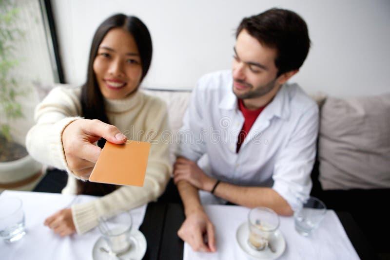 Gelukkig paar die voor maaltijd met kaart bij restaurant betalen stock foto