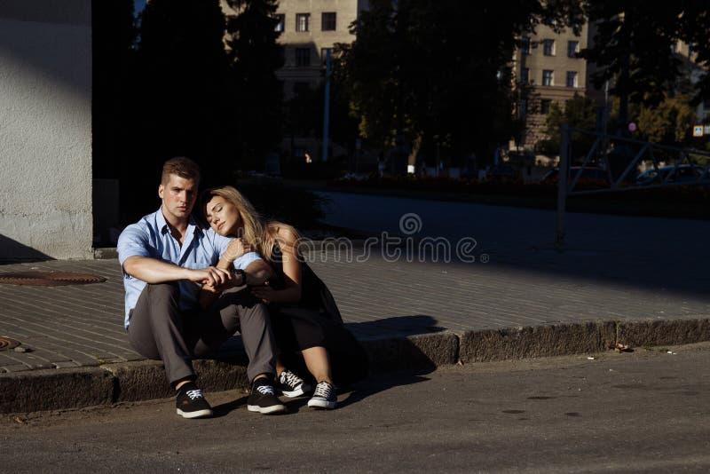 Gelukkig paar die zitting op bardure in de stad koesteren de donkere achtergrond, de zon glanst op minnaars royalty-vrije stock foto's