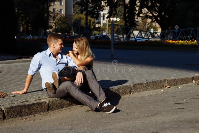 Gelukkig paar die zitting op bardure in de stad koesteren de donkere achtergrond, de zon glanst op minnaars royalty-vrije stock fotografie