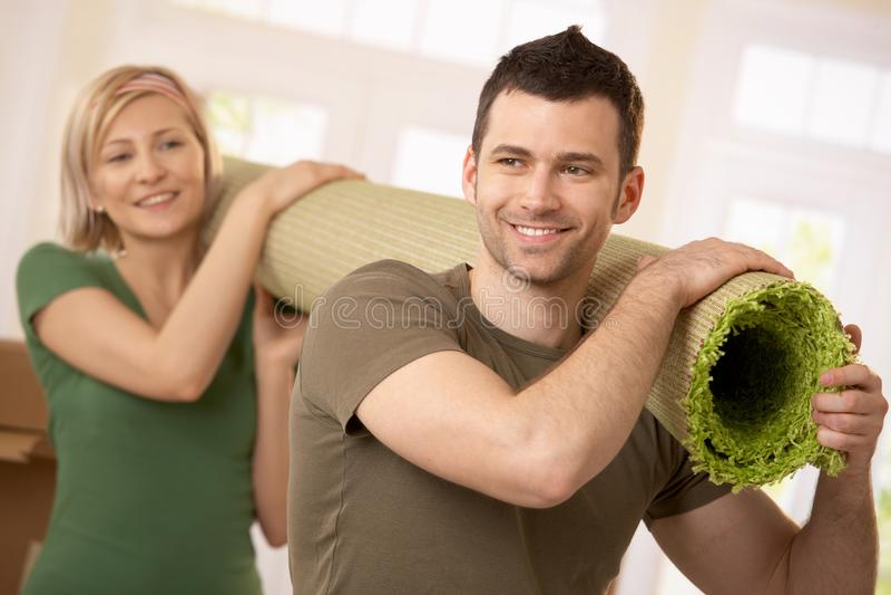 Gelukkig paar dragend tapijt samen stock afbeeldingen