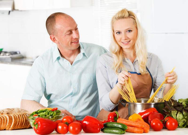 Gelukkig paar in hun keuken stock afbeelding