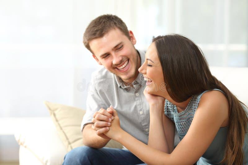Gelukkig paar of huwelijk die thuis lachen stock afbeeldingen