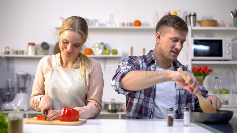 Gelukkig paar kokend diner samen bij keuken, gendergelijkheid in huishoudelijk werk stock afbeelding