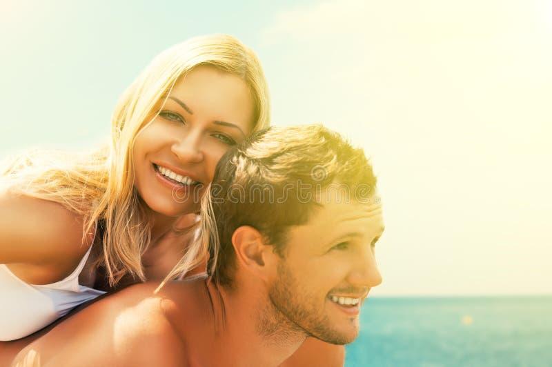 Gelukkig paar in liefde die en op het strand koesteren lachen royalty-vrije stock foto