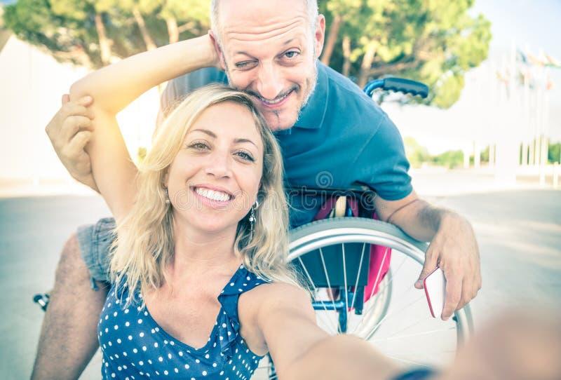 Gelukkig paar in liefde die selfie met rolstoel nemen stock afbeelding