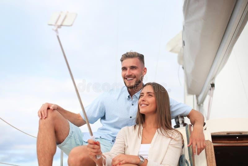 Gelukkig paar in liefde die selfie op varende boot nemen, die op een jacht bij het overzees ontspannen stock afbeeldingen