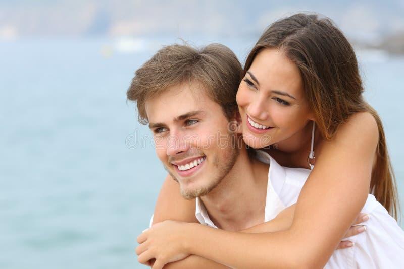 Gelukkig paar in liefde met perfecte glimlach op het strand stock afbeeldingen