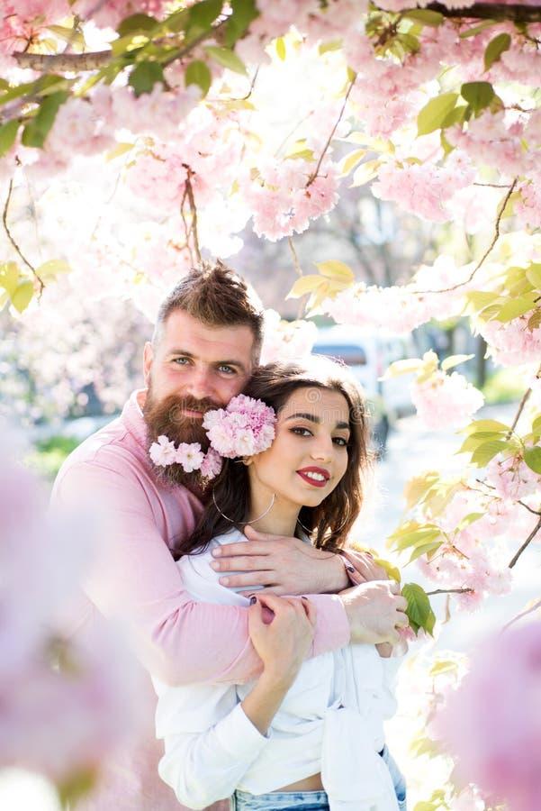 Gelukkig paar in liefde onder tot bloei komende bomen Gebaarde man omhelzings sensuele vrouw Rood nam toe Haar geluk is alles royalty-vrije stock afbeeldingen