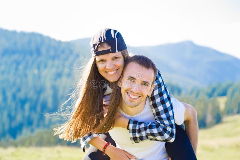 Gelukkig paar in liefdegang bovenop bergen De jonge gelukkige mens houdt zijn meisje royalty-vrije stock foto