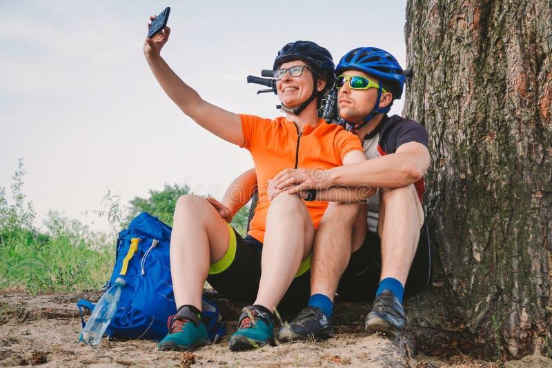 Gelukkig paar met bergfiets die selfie smartphone in openlucht nemen Een gelukkig paar, die een actieve levensstijl leiden, hield royalty-vrije stock fotografie