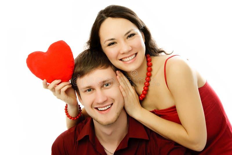 Gelukkig paar met een hart-vormig hoofdkussen stock afbeelding