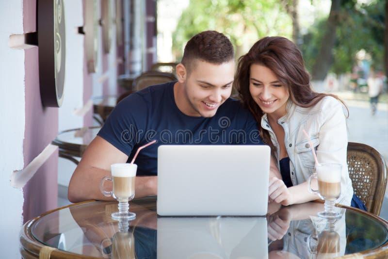 Gelukkig paar met laptop bij een koffie royalty-vrije stock foto