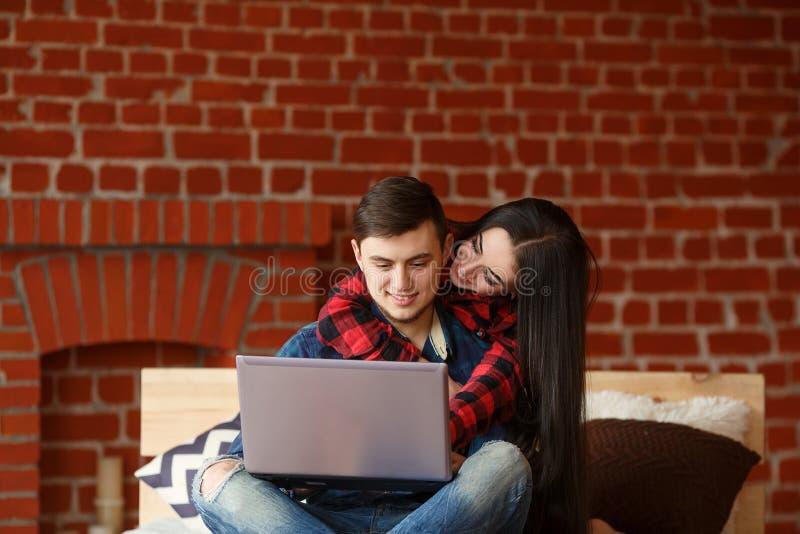 Gelukkig paar met laptop het besteden tijd samen thuis, het glimlachen van en het hebben van pret stock fotografie