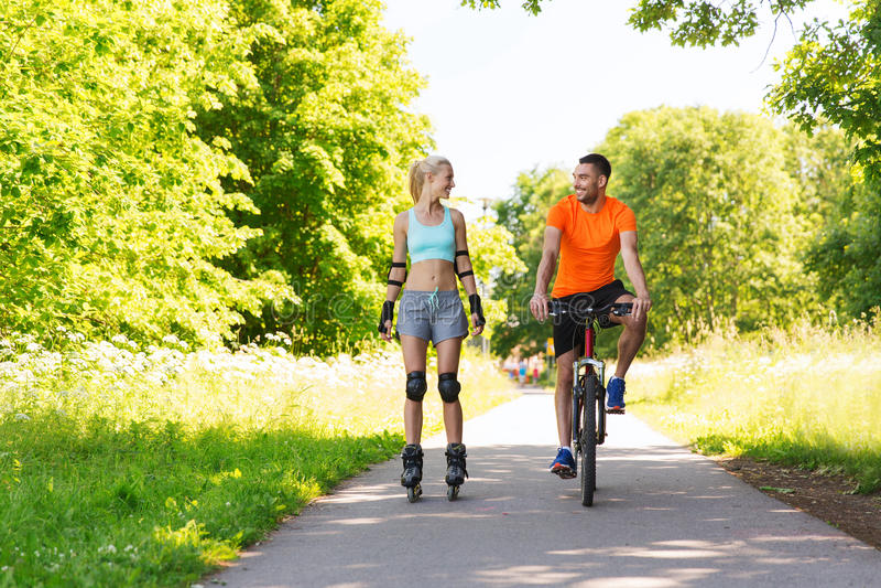Gelukkig paar met rollerblades en fiets het berijden stock foto's