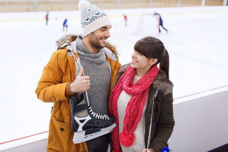 Gelukkig paar met schaatsen op het schaatsen piste stock fotografie