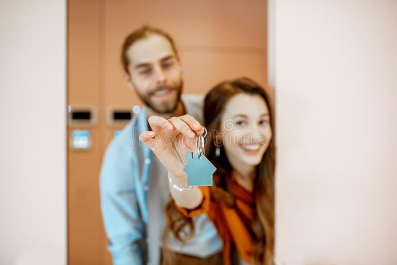 Gelukkig paar met sleutels bij de gang van een nieuwe flat royalty-vrije stock afbeelding
