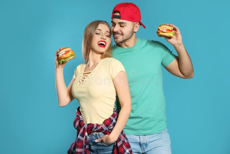Gelukkig paar met smakelijke burgers stock foto's