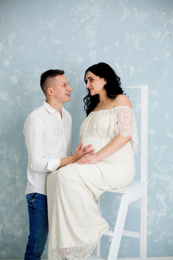Gelukkig paar met zwangere vrouw in witte kleding op de stoel stock foto