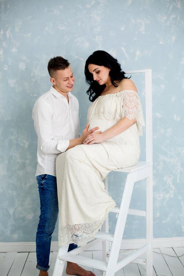 Gelukkig paar met zwangere vrouw in witte kleding op de stoel stock foto's
