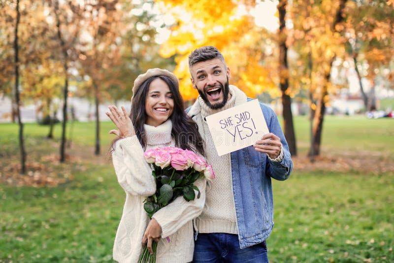 Gelukkig paar na het doen van voorstel in de herfstpark stock afbeeldingen