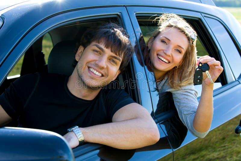 Gelukkig paar in nieuwe auto stock afbeelding