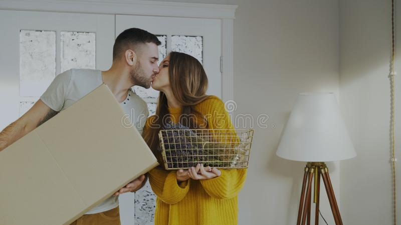 Gelukkig paar gelukkig om hun nieuw huis in eerste keer in te gaan Jonge mens die zijn meisje kust royalty-vrije stock afbeeldingen