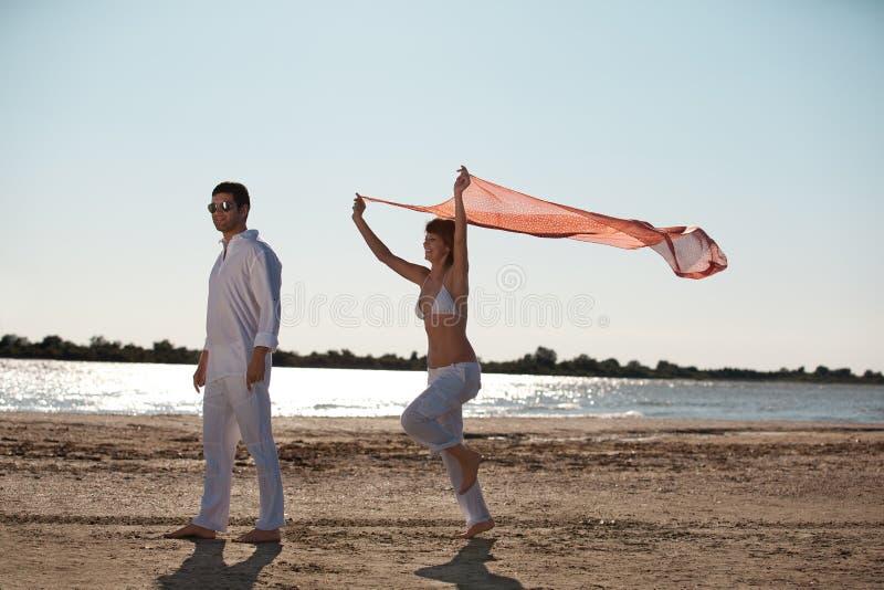 Gelukkig paar op de wind van de strandsjaal royalty-vrije stock foto's