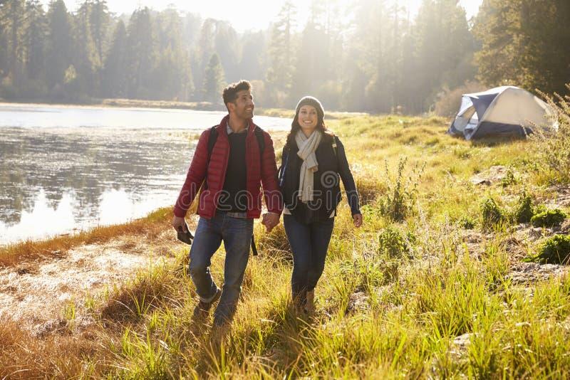 Gelukkig paar op een het kamperen reis die dichtbij een meer lopen stock afbeeldingen