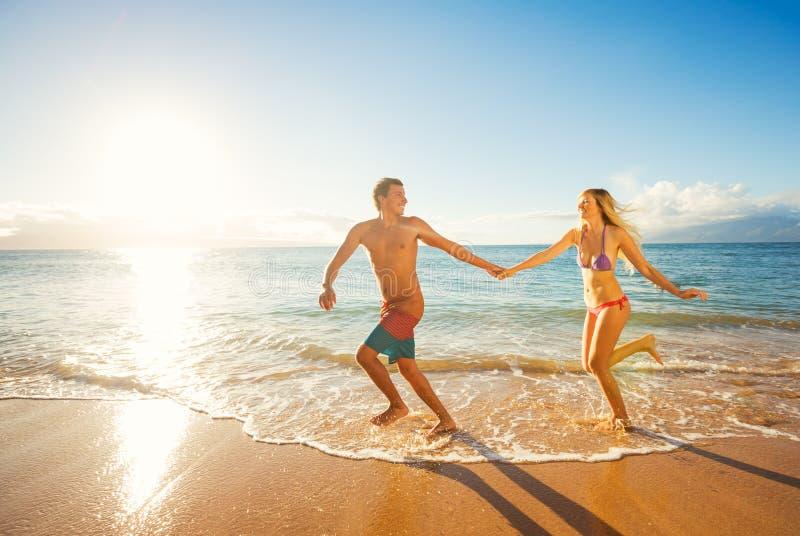 Gelukkig Paar op Tropisch Strand bij Zonsondergang royalty-vrije stock afbeelding