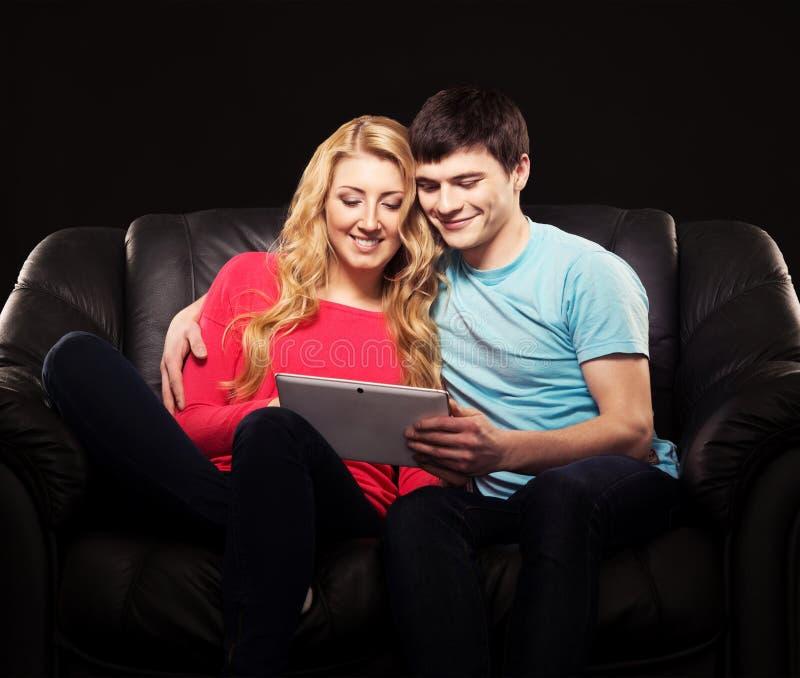Gelukkig paar samen op een bank met een tablet royalty-vrije stock afbeeldingen