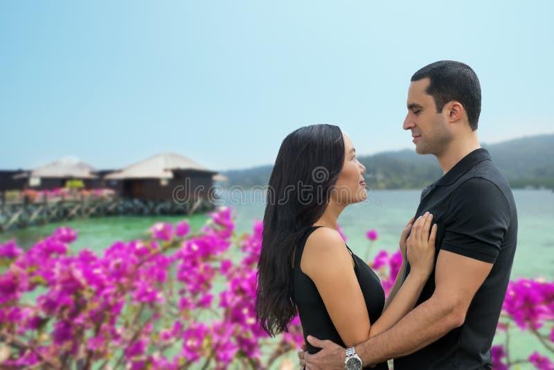Gelukkig paar tussen verschillende rassen in liefde op zee kant met bungalow backg stock foto's
