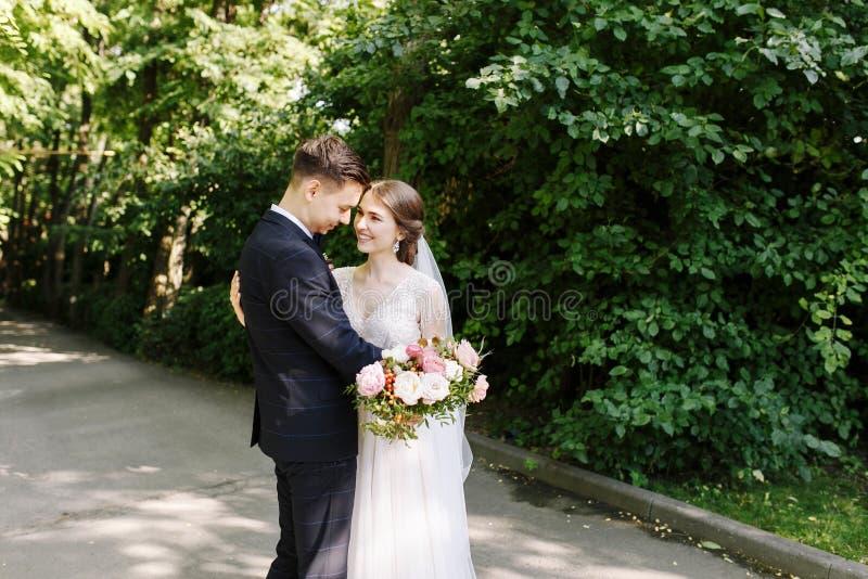 Gelukkig Paar van Bruid en bruidegom in park het kussen De gelukkige jonggehuwden bij huwelijk in aard groen bos kussen foto stock afbeelding
