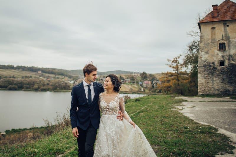 Gelukkig paar van jonggehuwden die bij zonsondergang met bac van de kasteelmuur kussen royalty-vrije stock foto's