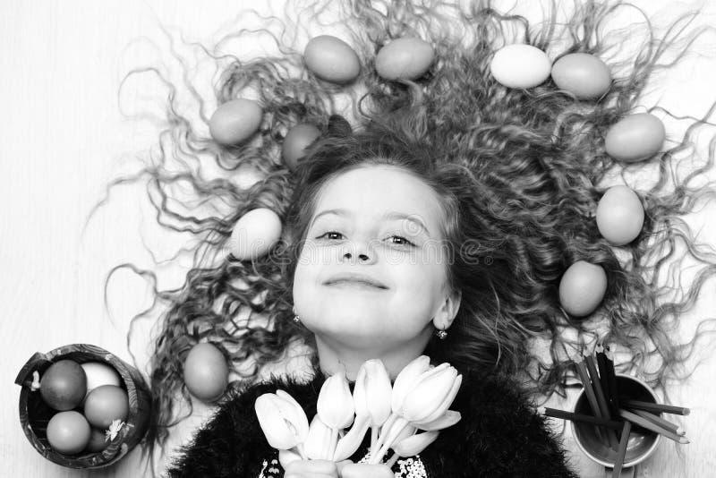 Gelukkig Pasen-meisje, kleurrijke eieren in lang haar, tulpenbloemen royalty-vrije stock foto's