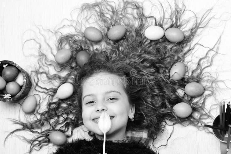 Gelukkig Pasen-meisje, kleurrijke eieren in lang haar, tulpenbloemen stock foto