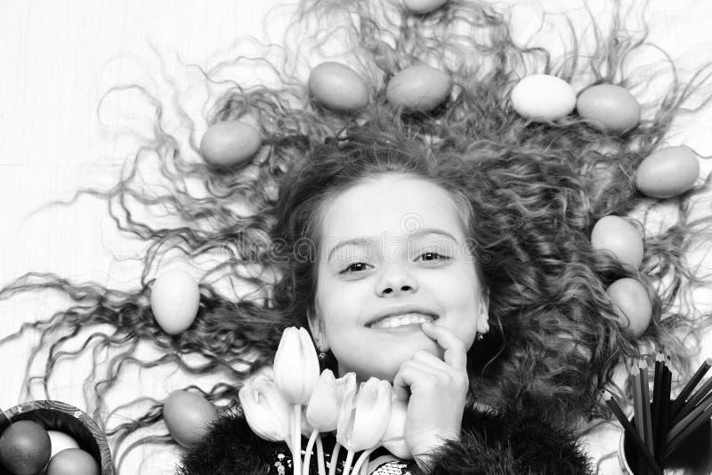 Gelukkig Pasen-meisje, kleurrijke eieren in lang haar, tulpenbloemen stock foto's