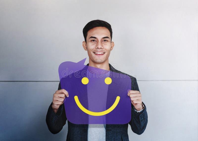 Gelukkig Persoonsconcept De jonge Mens die en toont Glimlachpictogram op de Kaart van de Toespraakbel glimlachen Positieve mensel stock fotografie