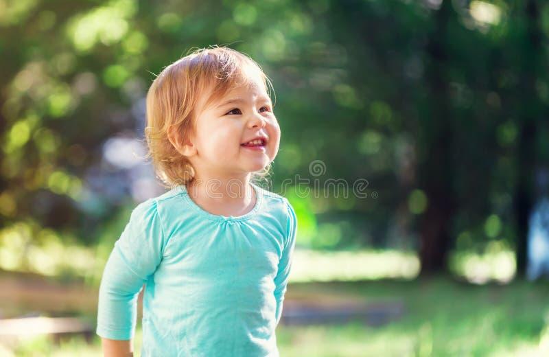 Gelukkig peutermeisje die buiten glimlachen stock afbeelding
