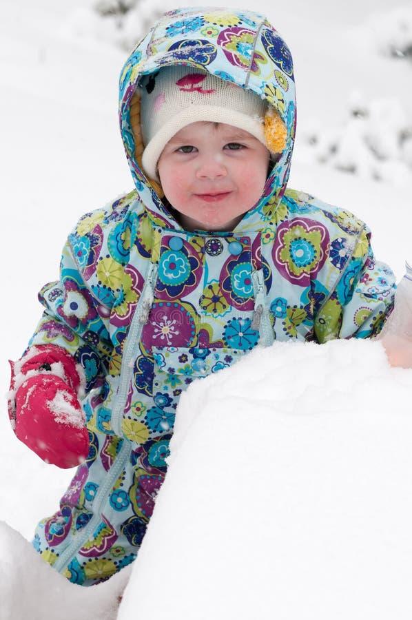 Gelukkig peutermeisje in warme laag en gebreide hoed die omhoog sneeuw werpen en een pret in de winter hebben buiten, openluchtpo royalty-vrije stock fotografie