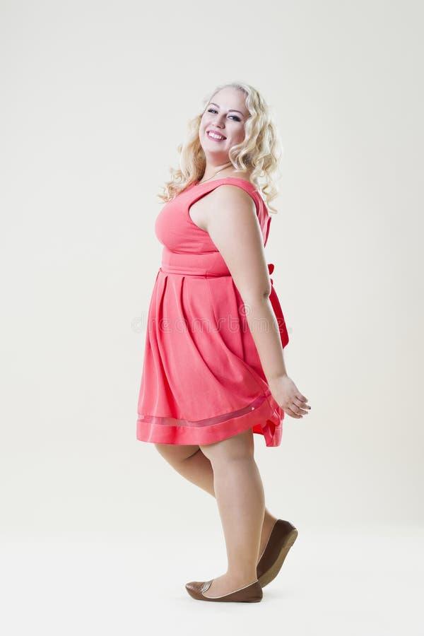 Gelukkig plus groottemannequin, sexy vette vrouw op beige achtergrond royalty-vrije stock afbeeldingen